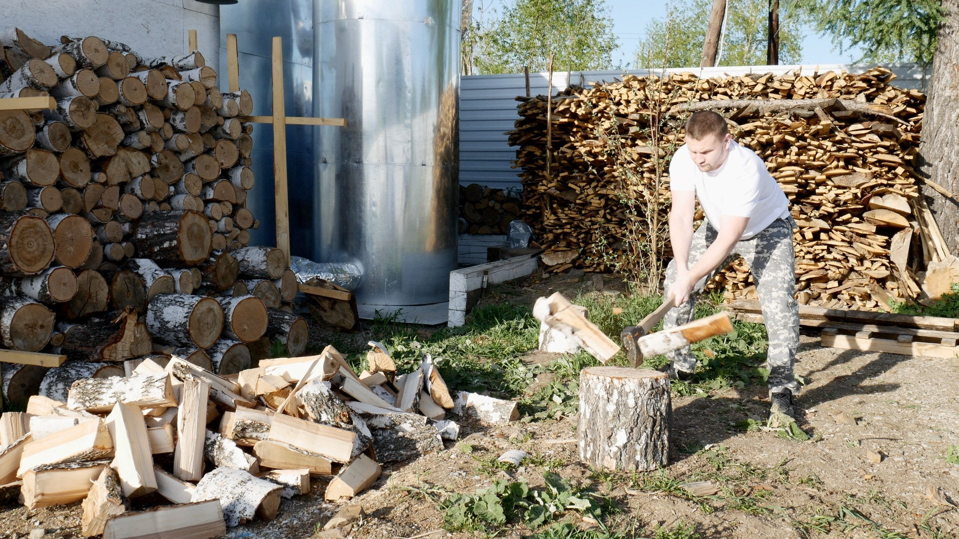 woman in white t-shirt and gray pants holding firewood